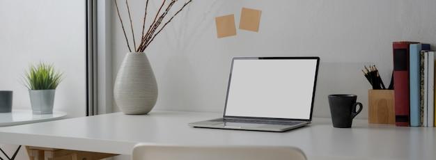 Beschnittene aufnahme des tragbaren arbeitsbereichs mit laptop, becher und dekoration
