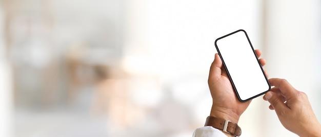 Beschnittene aufnahme von männlichen händen unter verwendung des smartphones schließen beschneidungspfad im unscharfen hintergrund mit kopierraum ein
