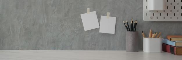 Beschnittene aufnahme von minimalem kopierraum mit schreibwaren und büchern auf weißem tisch