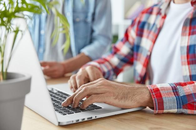Beschnittene aufnahme von zwei männlichen bloggern, die eine veröffentlichung auf einem laptop schreiben, einen laptop verwenden und am holzschreibtisch sitzen. junge wohlhabende geschäftsleute checken e-mails und senden rückmeldungen, die mit wlan verbunden sind