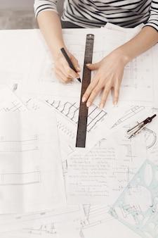 Beschnittene draufsicht der jungen schönen weiblichen architektenhände, die blaupausen mit lineal und stift auf weißem tisch im coworking space tun. unternehmenskonzept