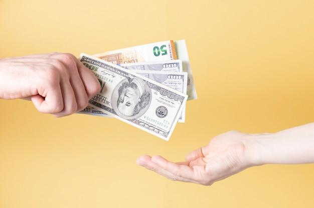 Beschnittene hände, die papierwährung vor gelbem hintergrund halten