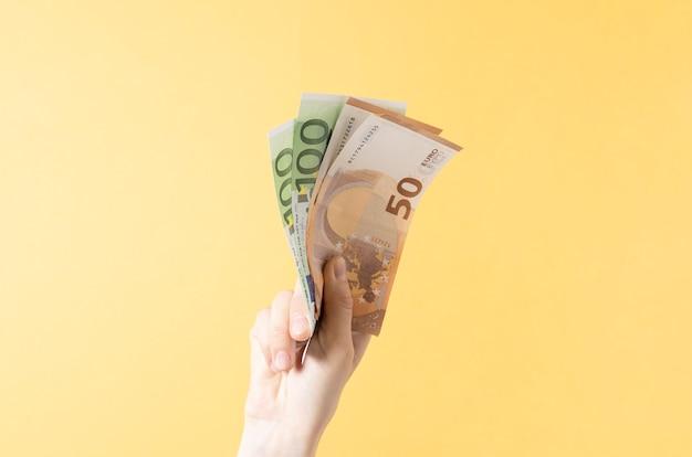 Beschnittene hand der frau, die papierwährungen auf gelbem hintergrund hält