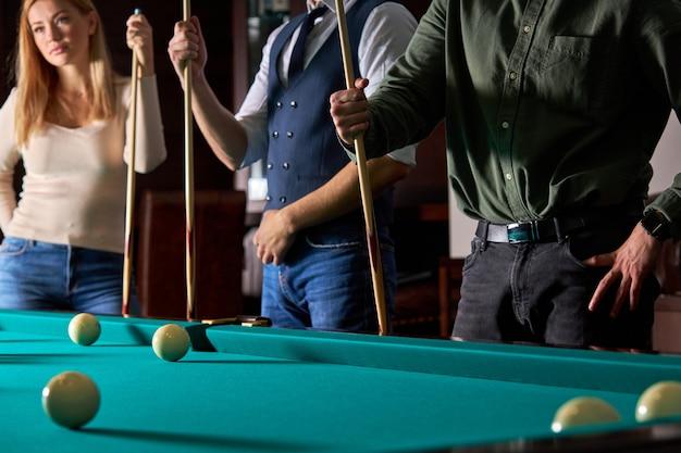 Beschnittene menschen, die zusammen stehen, lustiges billard, snooker oder billard spielen, genießen die freizeit. spaß, billard, freizeit, ruhekonzept