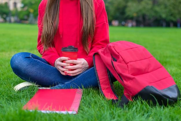 Beschnittene nahaufnahme des glücklichen positiven mädchens, das perfektes heißes getränk genießt, das hausaufgaben nahe highschool tut