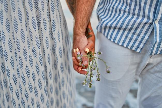 Beschnittene nahaufnahme eines paares, das hände mit wildblumen vor dem meer hält.