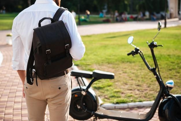 Beschnittene rückansicht des mannes mit rucksack, der nahe dem modernen motorrad draußen steht