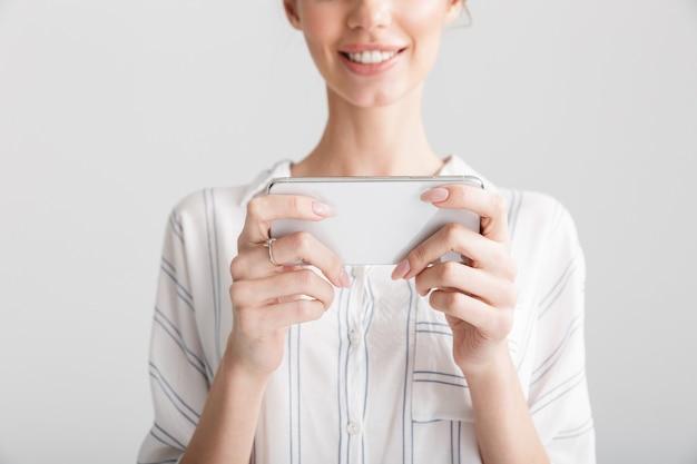 Beschnittene schöne frau, die lächelt und ein videospiel auf dem handy spielt, isoliert auf weißem hintergrund