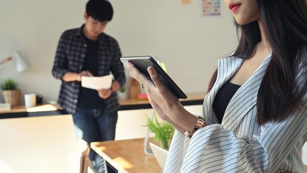 Beschnittene schuss weibliche kreativität, die ihren tablet-computer im büro betrachtet.
