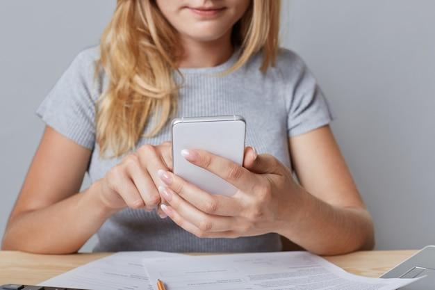 Beschnittene schussansicht der blonden unternehmerin hält smartphone, umgeben von dokumenten, empfängt nachrichten