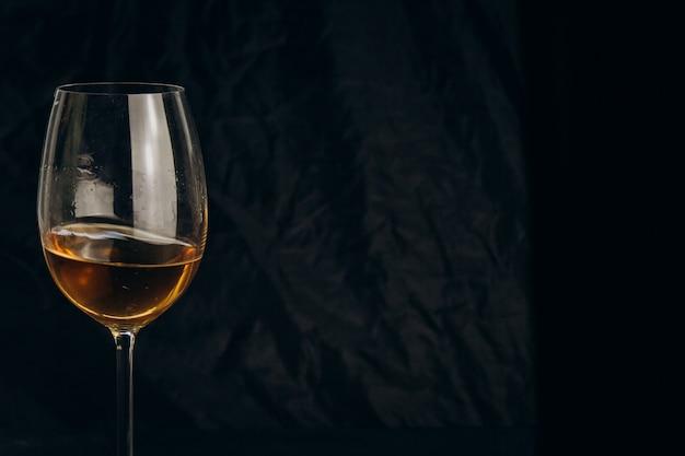 Beschnittene weibliche hand, die ein glas weißwein auf einem schwarzen hintergrund hält. nahaufnahme des alkoholischen getränks.