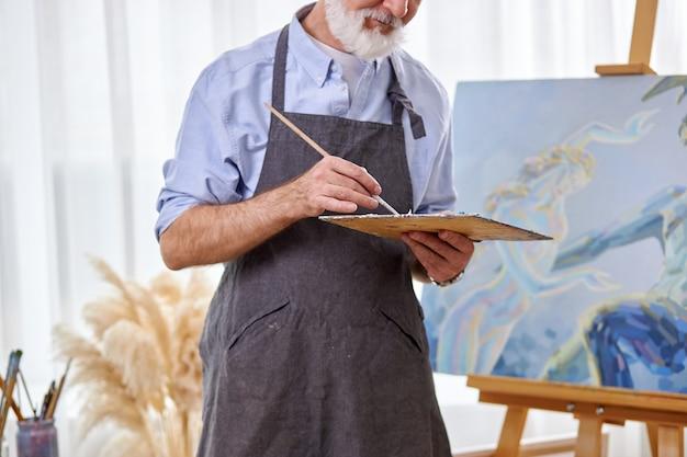 Beschnittener künstler, der farbe mit pinsel von einer palette nimmt, auf leinwand zeichnet, ölgemälde