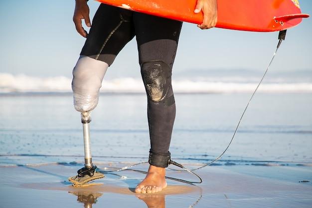 Beschnittener männlicher surfer, der mit surfbrett am meeresstrand steht
