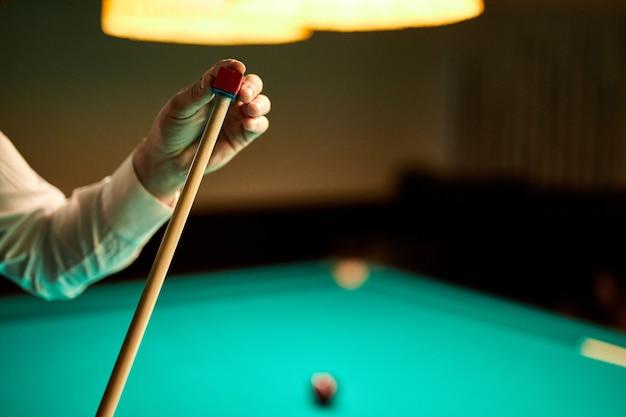 Beschnittener mann, der billard-stichwort für spiel, nahaufnahmefoto der hände vorbereitet. snooker spielen
