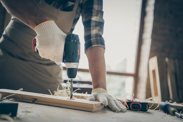 Beschnittener mann, der holz mit handschuhen bohrt und seine arbeit drinnen mit modernen instrumenten erledigt