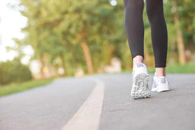 Beschnittener schuss der beine einer fitnessfrau, die im wald-copyspace-sportmotivationsenergie-ausdauersport-cardio-trainingskonzept läuft.