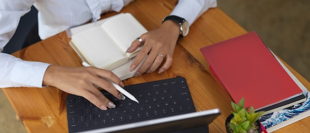 Beschnittener schuss der frau, die mit digitalem tablett und briefpapier auf holztisch arbeitet