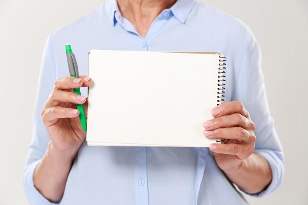 Beschnittener schuss der frau in der freizeitkleidung, die notebook lokalisiert hält