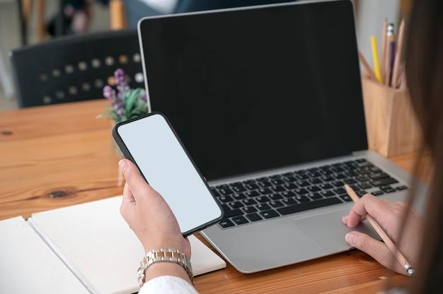 Beschnittener schuss der frauenhand, die smartphone des leeren bildschirms beim arbeiten am laptop-computer hält.