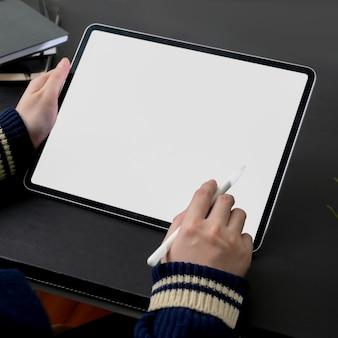 Beschnittener schuss der freiberuflerin, die auf tablett mit leerem bildschirm arbeitet