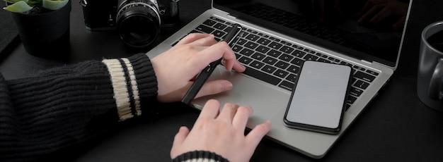 Beschnittener schuss der geschäftsfrau, die am laptop arbeitet, während informationen auf smartphone suchen