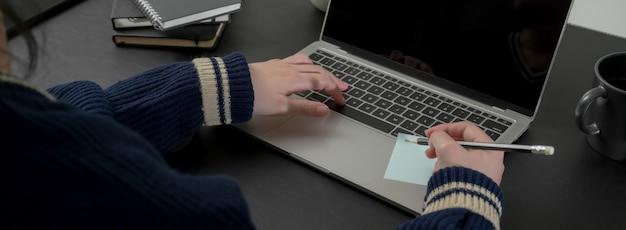Beschnittener schuss der geschäftsfrau, die eine idee auf notizblock schreibt, während informationen suchen