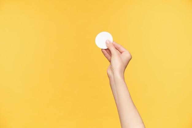 Beschnittener schuss der hand der jungen hübschen frau, die weißes wattepad mit den fingern hält, während über orange hintergrund lokalisiert wird. menschliche hände und schönheitskonzept