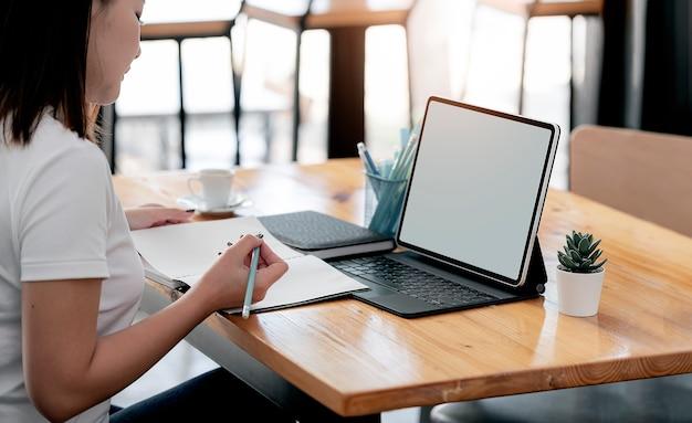 Beschnittener schuss der jungen asiatischen frau, die auf notizbuch schreibt und auf tablet-computer arbeitet, während im café sitzt.