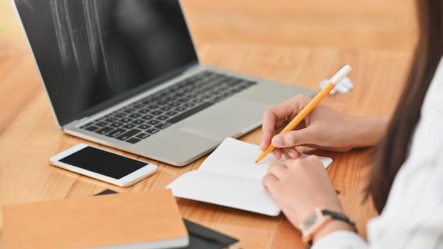 Beschnittener schuss der jungen geschäftsfrau, während sie notizen vor dem laptop mit dem schwarzen bildschirm auf dem hölzernen schreibtisch am arbeitsplatz machen.