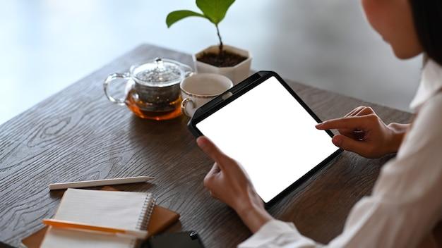 Beschnittener schuss der lässigen frau, die im café sitzt und digitales tablett verwendet.