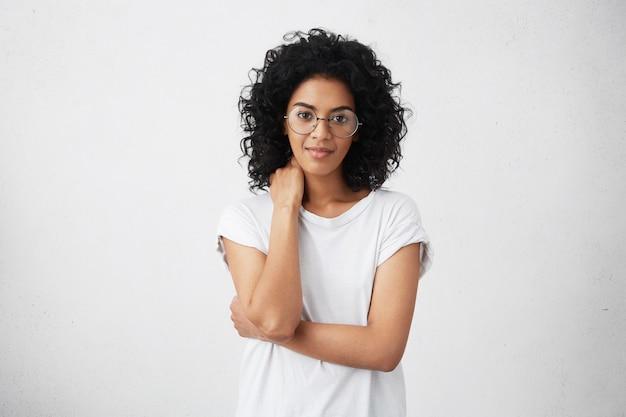 Beschnittener schuss der schönen freundlichen niedlichen lächelnden jungen afroamerikanerin, die mit geschlossener haltung, leicht lächelnd, mit schüchternem blick, brille tragend aufwirft. menschliche gefühle und gesten