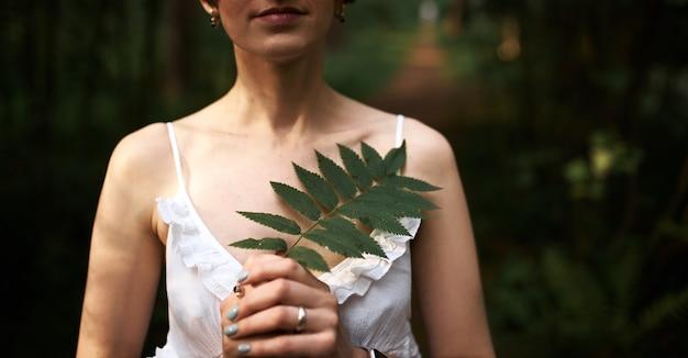 Beschnittener schuss der schönen zarten jungen braut im romantischen weißen kleid, das gegen grünen waldhintergrund aufwirft, farnblatt an ihrer brust hält. nicht erkennbare frau, die draußen unter pflanzen entspannt