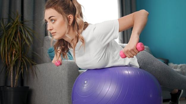 Beschnittener schuss der schönheit mit hanteln in den armen, die an den ellbogen gebogen werden, die auf fitnessballtraining zu hause liegen