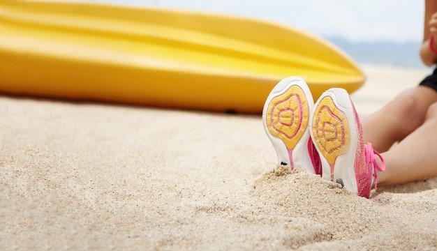 Beschnittener schuss der sportlerin, die rosa laufschuhe trägt, die auf sandstrand nach aktiver übung am meer sitzen. joggerin der frau, die draußen während des morgendlichen trainings entspannt. selektiver fokus auf sohlen
