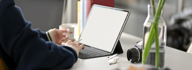 Beschnittener schuss der studentin, die auf digitalem tablett auf weißem arbeitstisch tippt