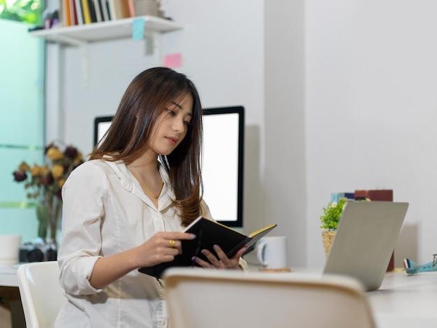 Beschnittener schuss der weiblichen büroangestelltenarbeit von zu hause mit laptop und computer im heimbüroraum
