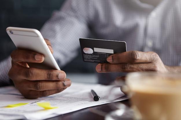 Beschnittener schuss des afroamerikanischen geschäftsmannes, der mit kreditkarte online zahlt