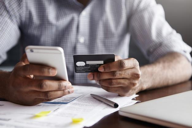 Beschnittener schuss des afroamerikanischen mannes, der rechnung im restaurant mit online-zahlungstechnologie bezahlt