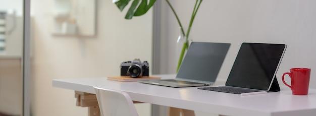 Beschnittener schuss des bequemen schreibtischs mit laptop, digitalem tablett, becher, kamera, büromaterial und dekoration