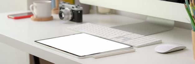 Beschnittener schuss des bequemen schreibtischs mit tablett des leeren bildschirms und computergeräten