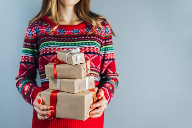 Beschnittener schuss des blonden mädchens mit den roten polierten nägeln, die bündel von geschenkboxen halten, die in bastelpapier eingewickelt werden