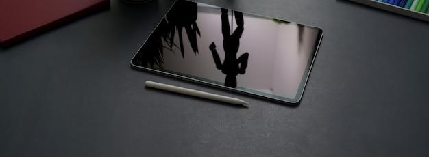 Beschnittener schuss des dunklen konzeptschreibtischs mit digitalem tablett, stift und büromaterial