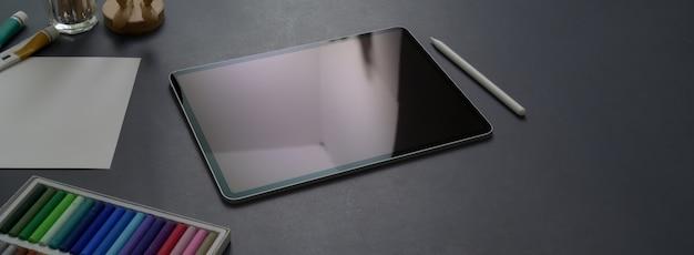 Beschnittener schuss des dunklen konzeptschreibtischs mit digitalem tablett, stift und designerbedarf
