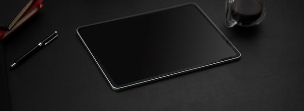 Beschnittener schuss des dunklen modernen arbeitsbereichs mit digitalem tablett, kaffeetasse und anderen vorräten