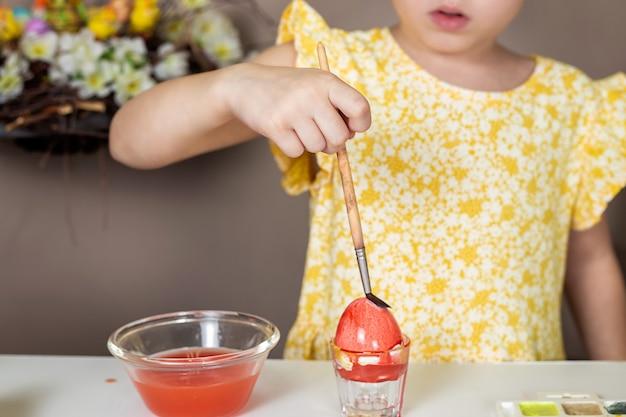 Beschnittener schuss des entzückenden kleinen mädchens, das ei für ostern malt.