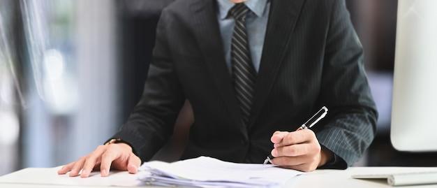 Beschnittener schuss des geschäftsmannes, der stift hält, der auf papierarbeit am schreibtisch unterschreibt.