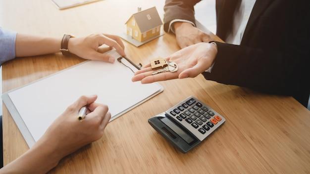 Beschnittener schuss des immobilienmaklers, der hausschlüssel zu seinem kunden hält