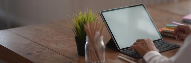 Beschnittener schuss des jungen college-studenten, der auf tablette tippt, während er im einfachen arbeitsbereich sitzt