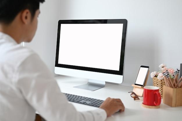 Beschnittener schuss des jungen mannes, der sein projekt auf computer-pc mit weißem bildschirm auf weißem schreibtisch plant.