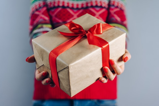 Beschnittener schuss des mädchens im gestrickten pullover mit traditionellem weihnachtsmuster, das geschenkbox hält, eingewickelt in bastelpapier und verziert mit rotem satinband